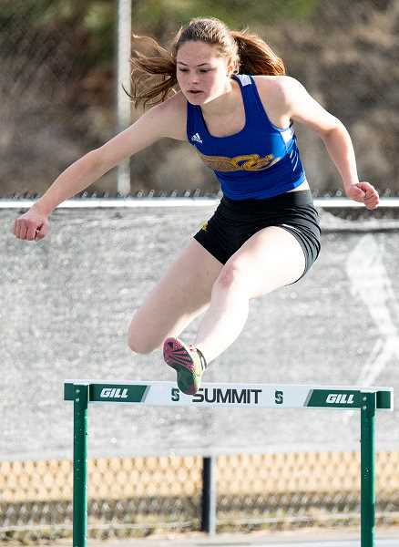 LON AUSTIN/CENTRAL OREGONIAN -  Mckinzee Mode goes over a hurdle during the 300-meter hurdle race Wednesday at Summit High School. Mode finished third in the event with a time of 52.76.