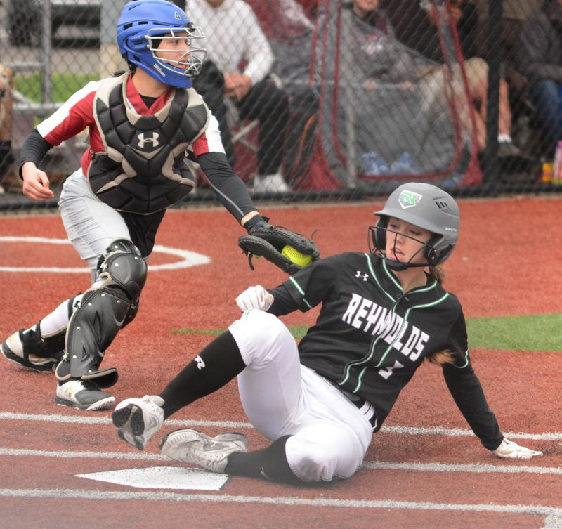 PMG PHOTO: DAVID BALL - Reynolds Hailey Burmeister slides in safely with the first run of the game in the third inning.