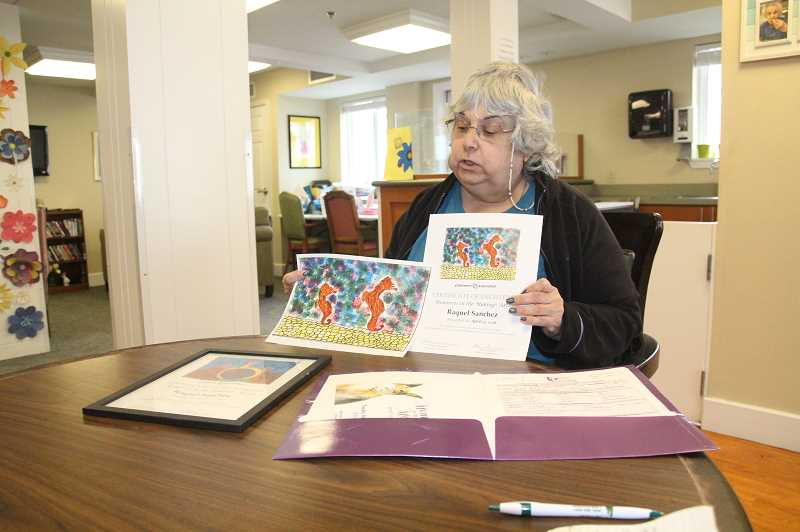 PMG PHOTO: JUSTIN MUCH - Raquel Sanchez displays some of her artwork. For several straight years the resident of Silver Creek Assisted Living in Woodburn has successfully submitted watercolor paintings to the Alzheimers Associations fundraising Memories in the Making auction and gala.