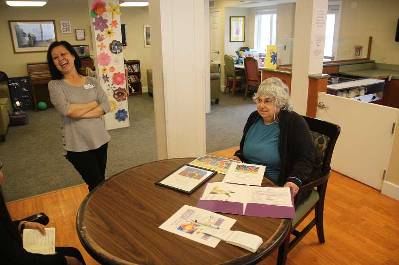 PMG PHOTO: JUSTIN MUCH - Raquel Sanchez, right, displays some of her artwork while visiting with Silver Creek Assisted Living activities director Jeannette Macauley, left. Sanchez has successfully submitted watercolor paintings to the Alzheimers Associations fundraising Memories in the Making auction and gala.