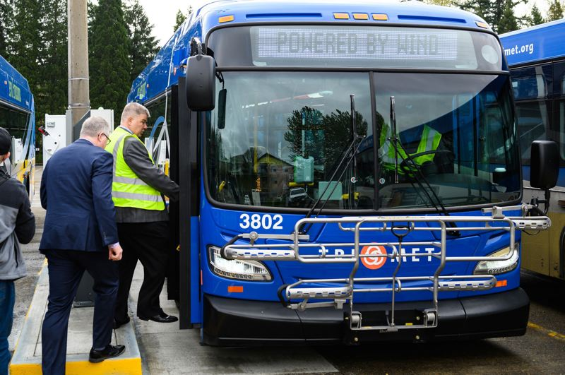 PMG PHOTO: CHRISTOPHER OERTELL - Riders board an electric bus for a first ride to the Sunset Transit Station during an unveiling ceremony at Trimets Merlo Garage facility in Beaverton on Tuesday.