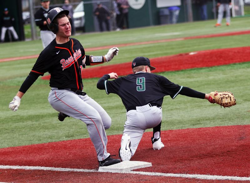 PMG PHOTO: DAN BROOD - Beaverton High School junior Jack Hanson (left) gets to first base as Tigard senior Sam Gerkman stretches to make a catch during Tuesday's game.