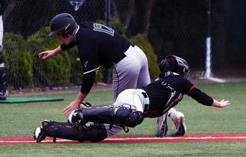 PMG PHOTO: DAN BROOD - Beaverton senior catcher Phoenix Forrester tags out Tigard junior Tyler Penn on a stolen base attempt during Tuesday's non-league game.