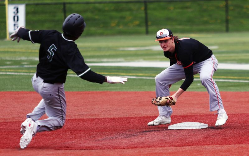 PMG PHOTO: DAN BROOD - Beaverton sophomore shortstop Trent Walker (right) gets ready to put a tag on Tigard sophomore Josh Schleichardt on a stolen base attempt during Tuesday's non-league game.