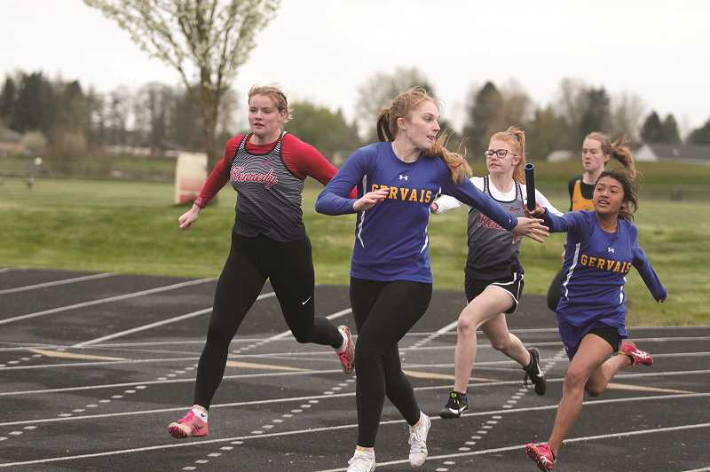 PMG PHOTO: PHIL HAWKINS - Sophomore Mary Davidson receives the baton handoff from teammate Judith Santos in the Cougars 4x100-meter victory at Gervais home meet on Thursday.