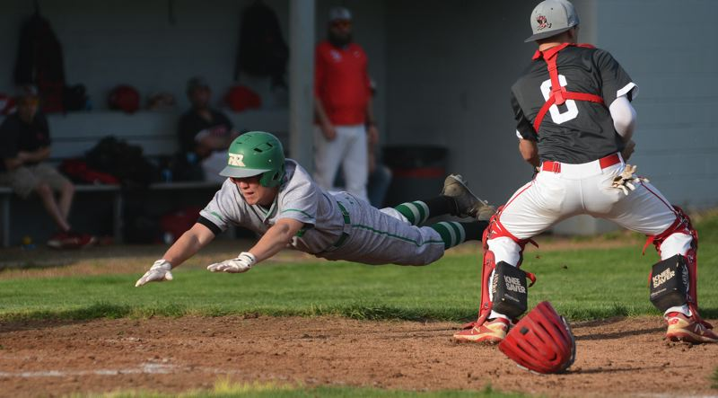 PMG PHOTO: DAVID BALL - Reynolds Nick Blegen dives head first to score to put the Raiders up 4-1 in the fifth inning of Thursdays win at David Douglas.