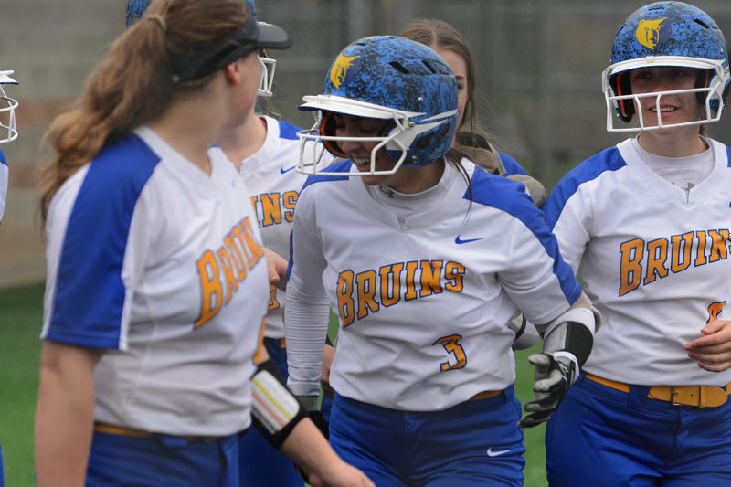 PMG PHOTO: DAVID BALL - Barlows Lexi Geary is greeted on her way back to the dugout after hitting her second home run to cap the Bruins 7-2 win at Clackamas on Friday.