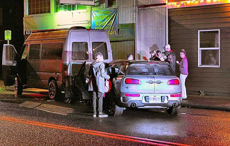 DAVID F. ASHTON - The returned occupants of the smashed Cooper Mini Coachman mill around their damaged car, while police talk sternly with the driver, who hit the parked van.