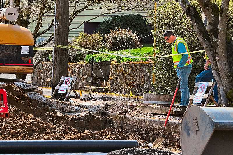 DAVID F. ASHTON -  A N.W. Natural Gas worker checks the area where an excavator sliced through a gas line in the Brooklyn neighborhood.
