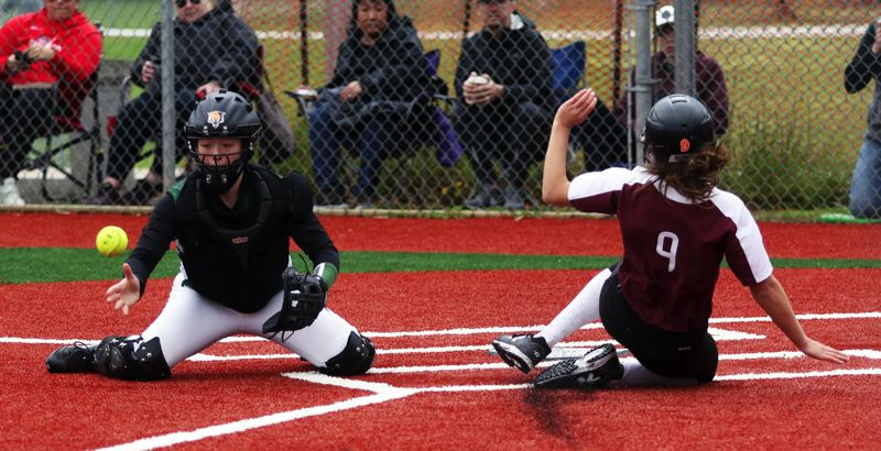 PMG PHOTO: DAN BROOD - Tualatin junior Sydney Wagner (right) slides home safely for the game's first run as Tigard junior catcher Emily Paulson reaches for the ball during Saturday's game.