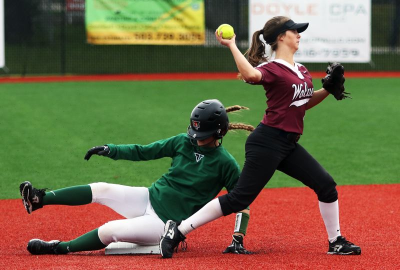 PMG PHOTO: DAN BROOD - Tualatin junior shortstop Bella Valdes (right) looks to make a throw to first after forcing out Tigard junior Abby Soderquist at second base during Saturday's game.