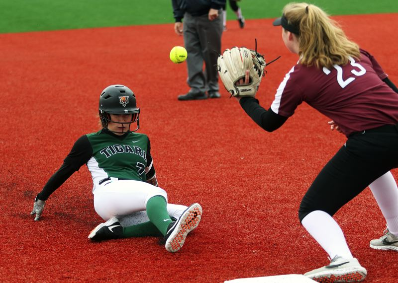 PMG PHOTO: DAN BROOD - Tigard junior Lexi Klum (left) slides to third base as Tualatin freshman Ella Hoyle catches the ball during Saturday's game.
