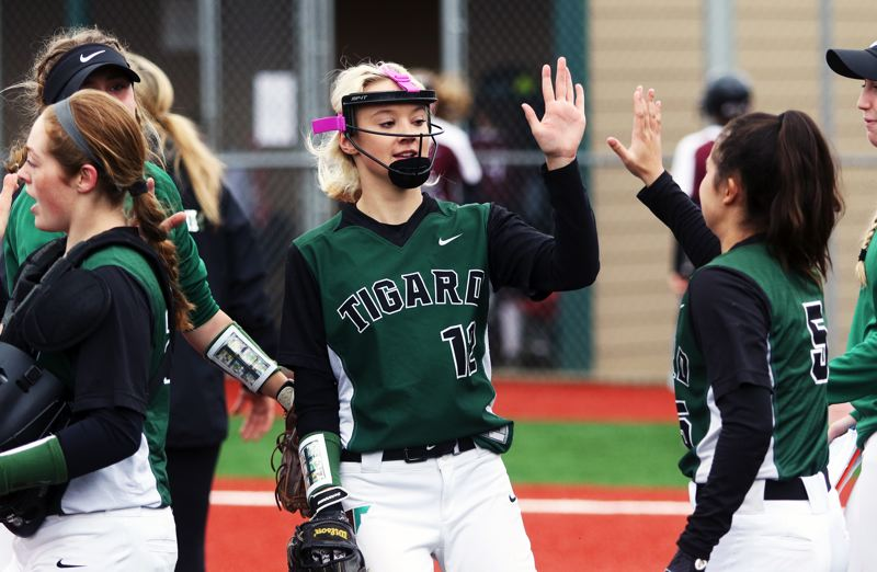 PMG PHOTO: DAN BROOD - Tigard freshman pitcher Makenna Reid in congratulated by her Tiger teammates between innings of Saturday's game.
