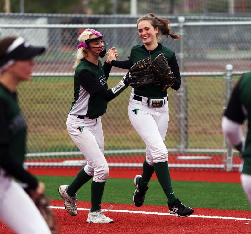 PMG PHOTO: DAN BROOD - Tigard freshmen Makenna Reid (left) and Eliot Miner celebrate following Miner's sliding catch of a foul ball during the Tigers' 3-1 win over Tualatin on Saturday.