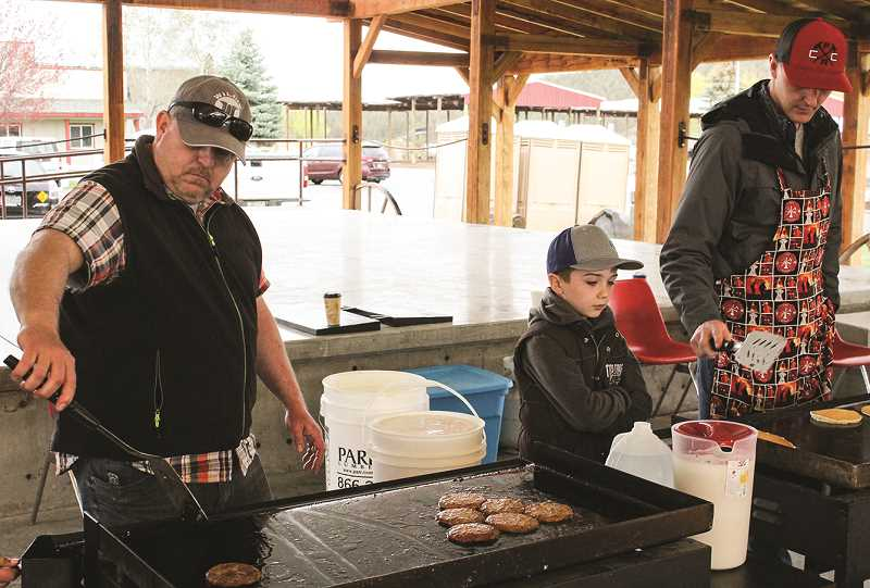 JASON CHANEY/CENTRAL OREGONIAN  - Denny Baulderee, left, Cash Tracy and Joe Mills serve a pancake breakfast during the Prineville Volunteer Fire Company fundraiser. Austin said the turnout was fantastic.
