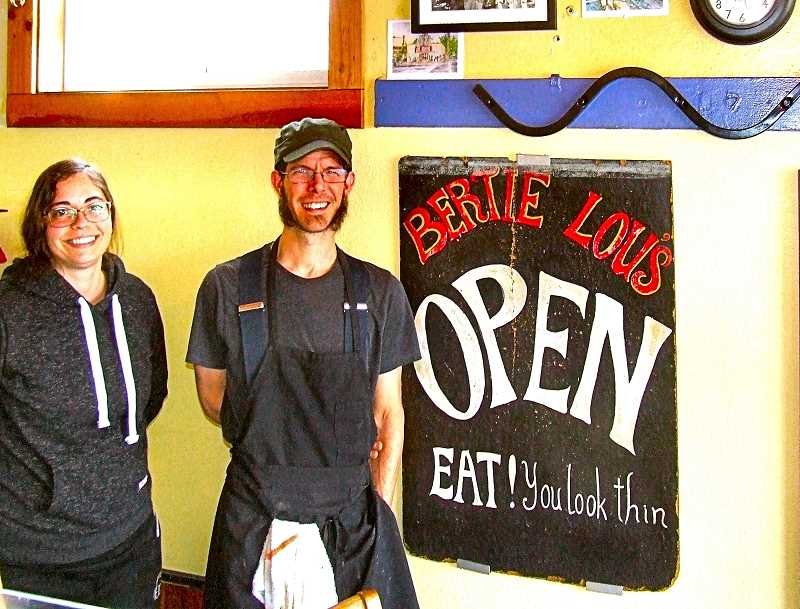 DANA BECK - Heres the current owner and galley cook, Daniel Gaard, with waitress Emily Schoon, in front of one of three original sandwich boards that once sat on the sidewalk outside Bertie Lous. A trip to Bertie Lous today is still a step back into the old Sellwood neighborhood, when industrial workers and military servicemen lined the half-moon-shaped counter for breakfast and lunch.