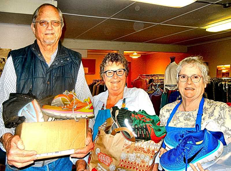 ELIZABETH USSHER GROFF - At the Mustard Seed Thrift Store in Woodstock, David Groff brings lightly used athletic shoes to All Saints volunteers Sonja Miller and Micky Keiter - for them to add to St. Francis Closet.