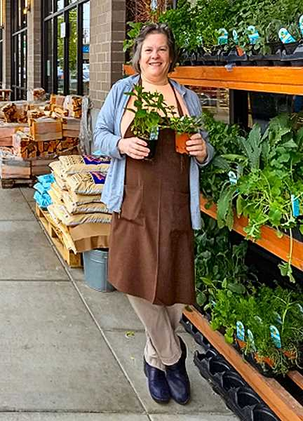 BECKY LUENING - Community volunteer extraordinaire Peggy McCafferty - standing in front of the Woodstock New Seasons store, which provides her with her day job.