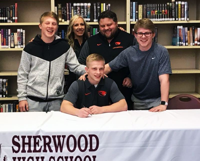 SUBMITTED PHOTO - Sherwood High School senior Gaven Jolley, surrounded by his family, signs his letter of intent to wrestle for Oregon State University.