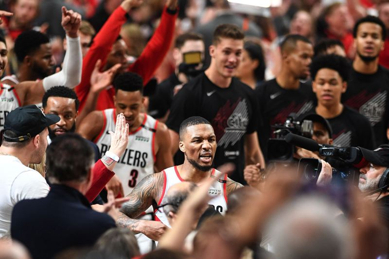 PMG PHOTO: CHRISTOPHER OERTELL - Damian Lillard of the Trail Blazers goes through teammates and fans after hitting the winning shot at the buzzer to beat Oklahoma City on Tuesday night at Moda Center. His deep 3 gave Portland a 118-115 victory and 4-1 first-round playoff series win over the Thunder.