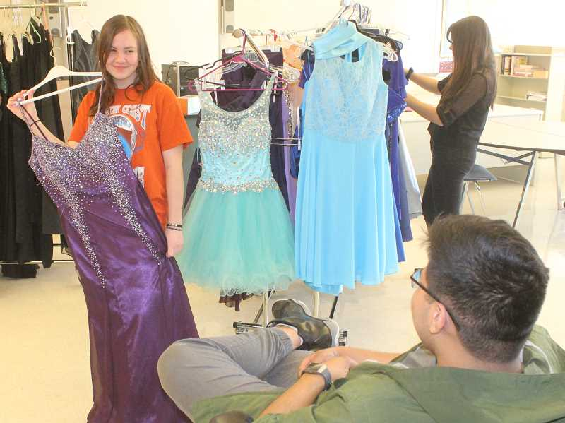 PHOTO BY SUSAN MATHENY - Madras High School senior Allison DeRoo asks for an opinion on her dress selection from Miguel Santellano, who was helping out at the dress giveaway.