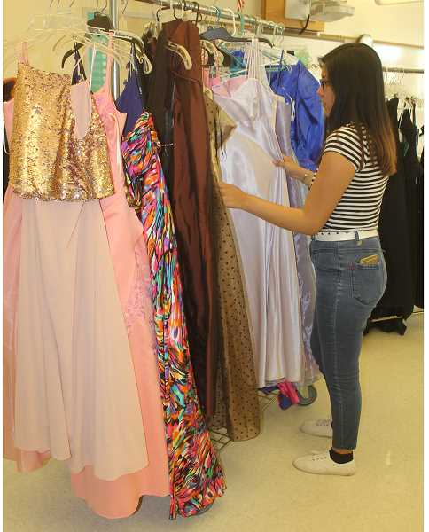 PHOTO BY SUSAN MATHENY - Aiyana Kalama checks out the racks of prom dresses.