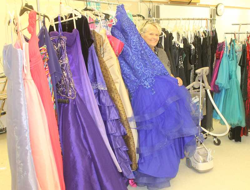 PHOTO BY SUSAN MATHENY - Peeking out of the dresses is Juanita Payton, a Madras High School teacher, who makes it one of her passions to collect prom dresses that she makes available to students who might not otherwise be able to afford one.