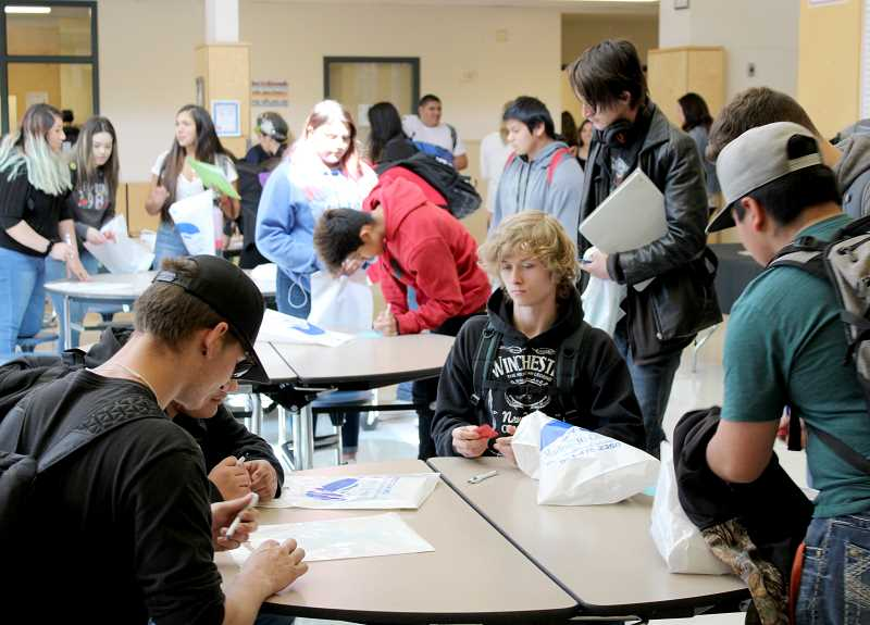 JENNIFFER GRANT/MADRAS PIONEER - Students gather and review paperwork during the Jefferson County Career Fair at Madras High School April 17. More than 30 businesses took part in the event, which aimed to connect students with jobs and careers.