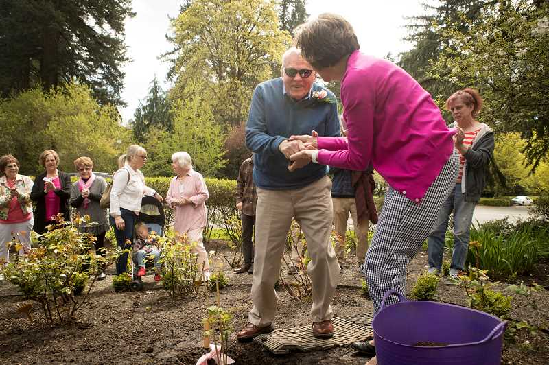 PGM PHOTO: JAIME VALDEZ - Allen Powers shakes hands with Linda Christenson after she helped him plant an Amazing Grace rose plant at Oswego Heritage House in honor of his late wife, Ann Powers, who was a longtime member of the Lake Grove Garden Club.The garden club will hold its 94th annual plant sale this Saturday, April 27.
