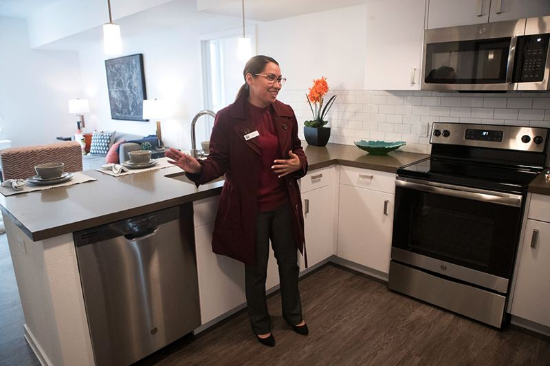 PMG PHOTO: JAIME VALDEZ - Onsite property manager Ana Trujillo shows off a typical kitchen and living room in the Rise Center.