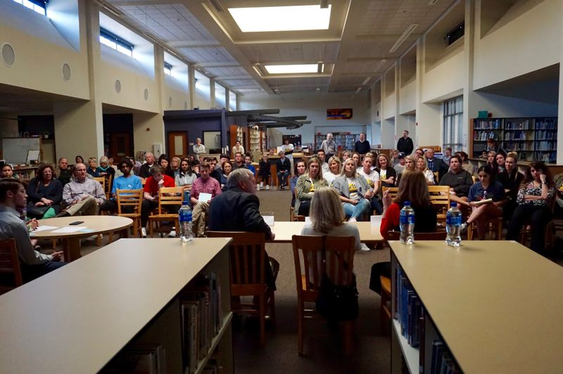 PMG PHOTO: CLAIRE HOLLEY - School board candidates John Wallin, Kelly Calabria and Kirsten Aird in front of a crowd of community members at Lake Oswego High School.