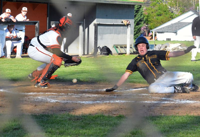 PMG PHOTO: MATT SINGLEDECKER - St. Helens sophomore Cody McKay slides across home plate against Scappoose during the Lions'  9-7 road victory on Wednesday.
