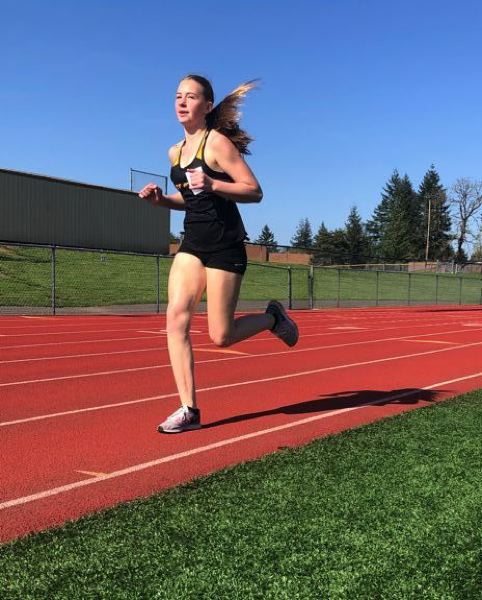PMG PHOTO: STEVE BRANDON - Mattie Miller, a St. Helens sophomore, is on her way to a PR and fourth place in the girls 1,500 during Wednesday's home meet.