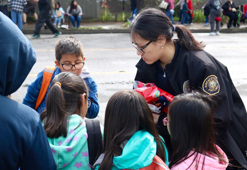 PMG PHOTO: ZANE SPARLING - Portland Police Bureau Cadet Jenny Pham hands out candy to kids during the 82nd Avenue of Roses Parade in Portland on April 27.