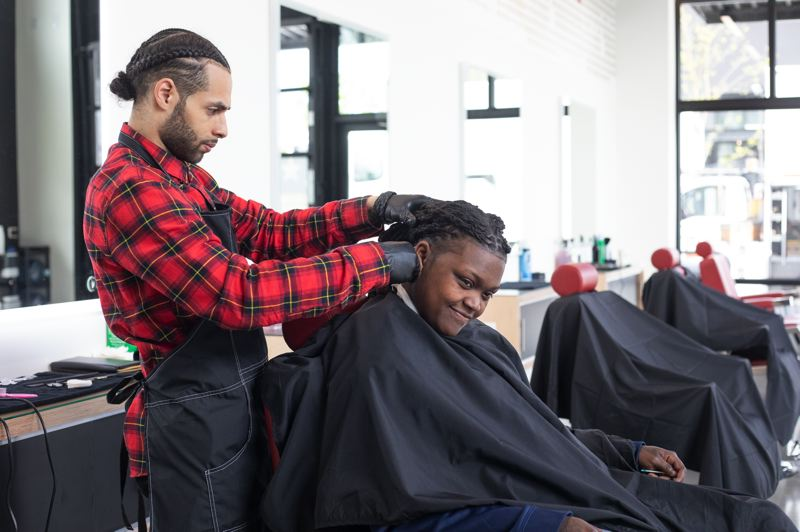 PMG PHOTO: JONATHAN HOUSE - Will Smith cuts the hair of Dominique King in Champions Barbershop at Alberta Commons.