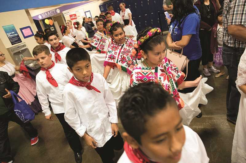 PMG PHOTO: JAIME VALDEZ - Youth follow one another to dance during the Dia de Niño event at Woodburn High School on Saturday.