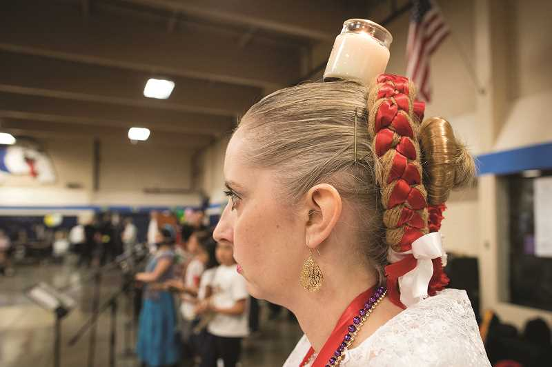 PMG PHOTO: JAIME VALDEZ - A candle sits on Leslie Leshs head before she dances during the Dia de Nino event at Woodburn High School.