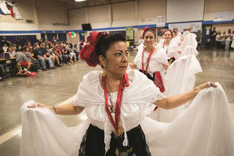 PMG PHOTO: JAIME VALDEZ - Rosa Floyd, a dance instructor for the dance group, Coscha Mestiza, leads her group in dance during the Dia de Nino event at Woodburn High School.