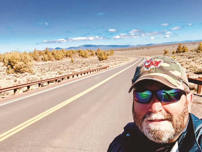 PHOTO SUBMITTED BY TOMMY ZURHELLEN - Tommy Zurhellen, shown on Millican Road, is walking across the country to raise awareness for veteran suicide and homelessness. He came through Prineville last week.