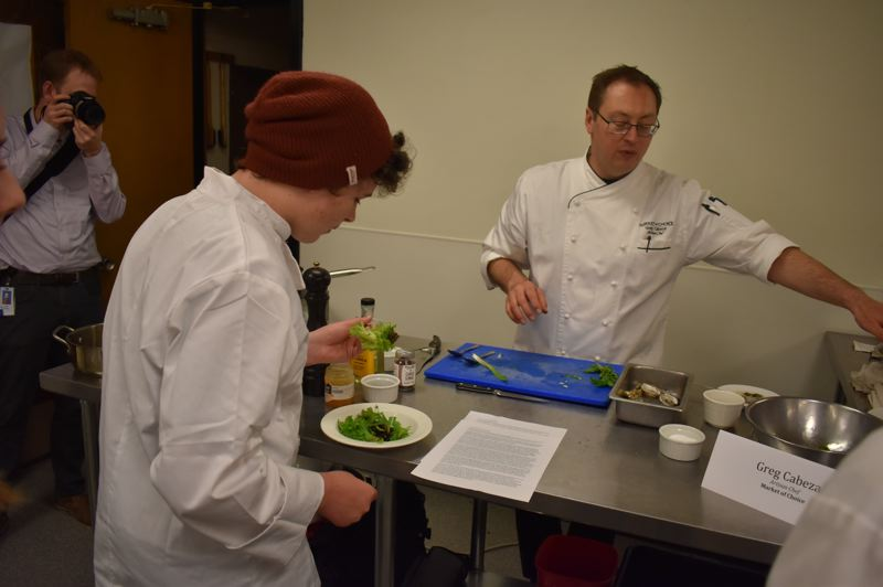 PMG PHOTO: RAYMOND RENDLEMAN - North Clackamas culinary student Phoenix Owen-Kennedy tries a salad made entirely with ingredients that Market of Choice chef Greg Cabeza found locally.