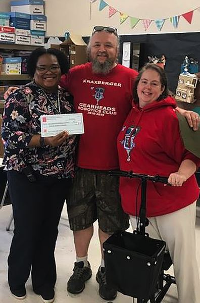 COURTESY PHOTO: LESLIE ROBINETTE - Principal Len Reed, left, accepts a check for Kraxberger Middle School from robotics coaches Shawn and Kelley Price. The funds were raised through the club's electronics recycling program.