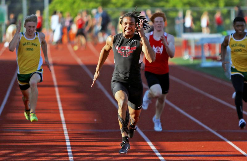 PMG PHOTO: DAN BROOD - Tualatin High School senior Dominique Loggins sprinted to victory in the 100-meter dash during the Wolves' league meet with Oregon City and West Linn.