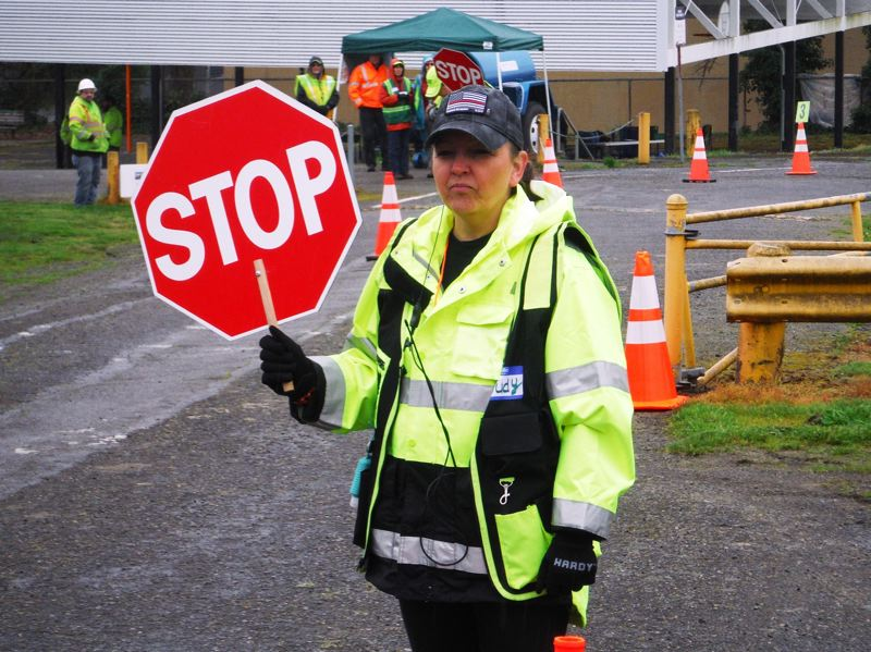 COURTESY PHOTO: OLWS - Judy Batt, leader of Milwaukie's Community Emergency Response Team, directs traffic at the April 13 drinking-water drill in Oak Lodge.