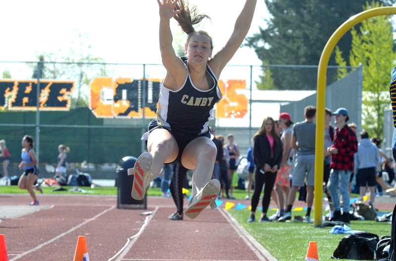 PMG PHOTO: TANNER RUSS - Canby heptathlete Ally Odell launches herself in the long jump.
