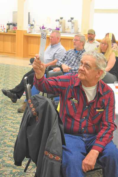 PMG PHOTO: EMILY LINDSTRAND - Glen Parsons bids on an item during the live auction at the Estacada Chamber of Commerces spring gala on Saturday, April 27.