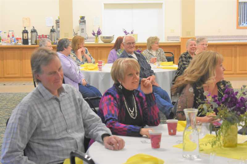 PMG PHOTO: EMILY LINDSTRAND - Spring gala attendees watch as items are bid on during the events live auction.