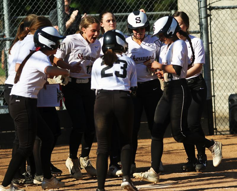 PMG PHOTO: DAN BROOD - Sherwood High School sophomore McKenzie Abiley (right) is greeted by her teammates at home plate after hitting a two-run home run in the win over Sprague.
