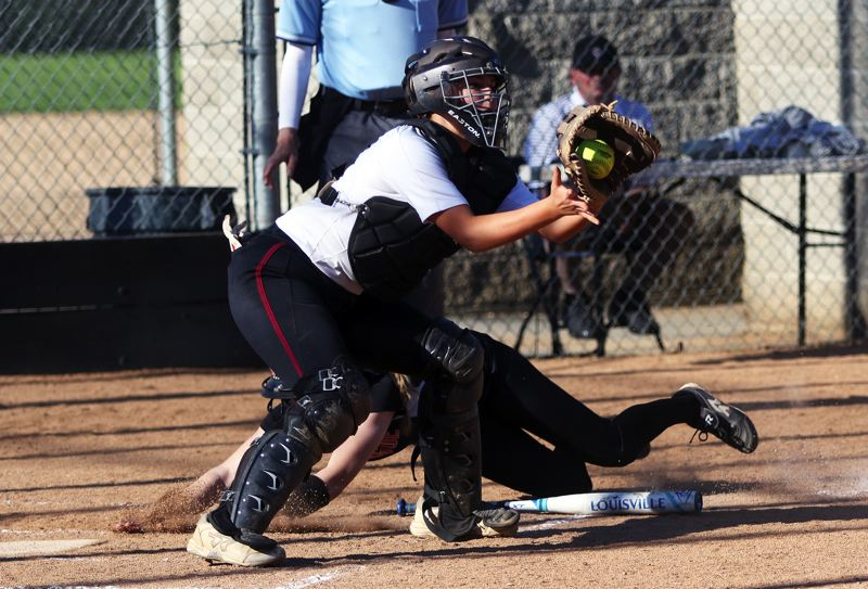 PMG PHOTO: DAN BROOD - Sherwood junior catcher Ema Kessler grabs the ball as a Sprague runner dives to the plate during the Lady Bowmen's 22-5 victory on Monday.