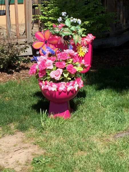 COURTESY PHOTO: LIZ NAUTA - Who can be mad about a spring-flowers toilet in their lawn?