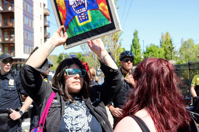 PMG PHOTO: ZANE SPARLING - KatMeow Garcia holds a painting of her grandmother during a May Day rally in Portland.